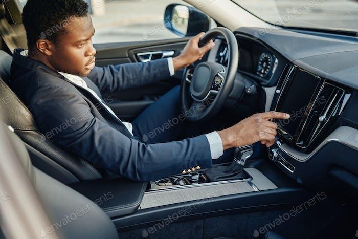 Black businessman inside car using car panel
