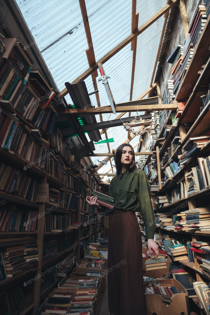 Girl standing in library with books