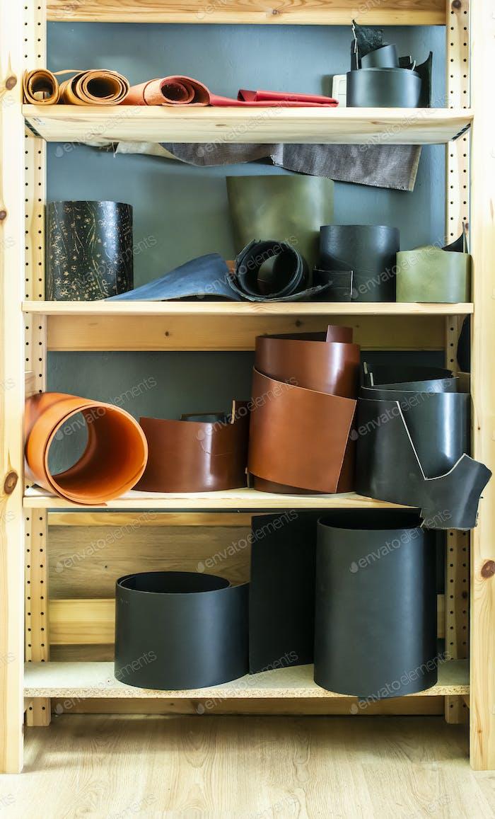 Viele Rollen Leder auf Regal in Lederwerkstatt.