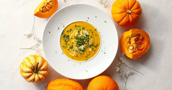 Pumpkin soup in plate with vegetables around