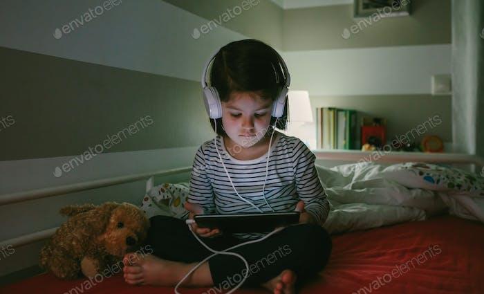 Mädchen mit Kopfhörern schaut auf das Tablet