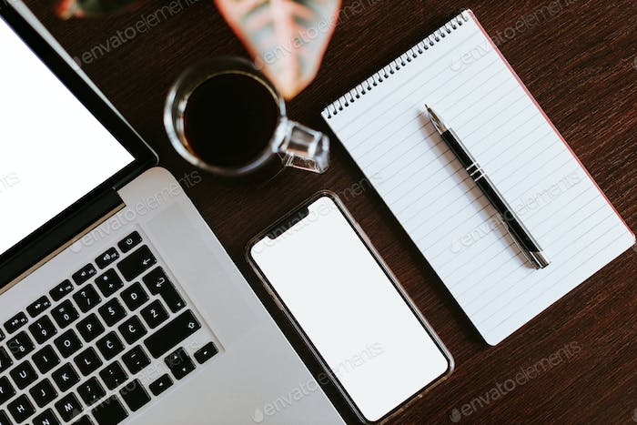 layout of laptop and phone with pen planning notebook