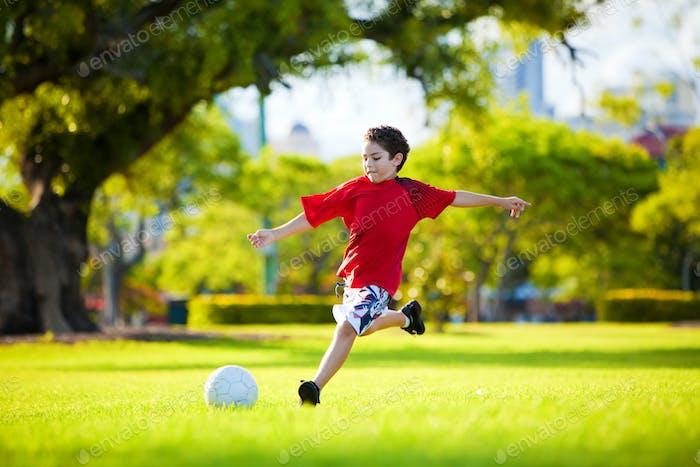 Junge aufgeregt Junge treten Ball im Gras