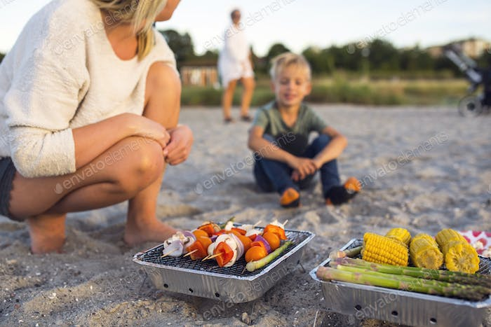 Mother and son (4-5) barbecuing on beach