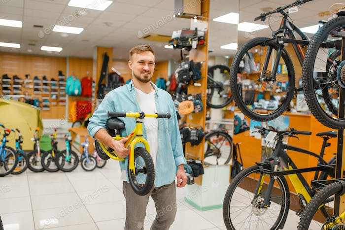 Young father with children's bicycle, shopping
