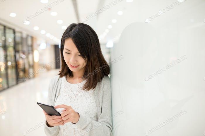 Frau benutzt Handy im Kaufhaus
