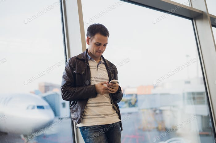 Traveler inside airport terminal. Young man using mobile phone and waiting for his flight.