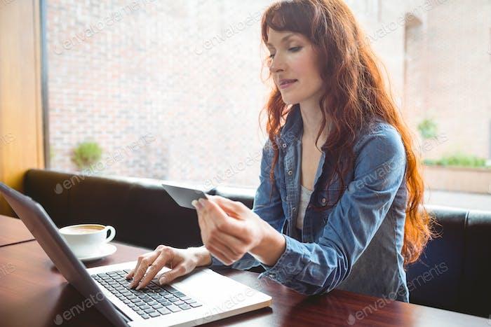 Student mit Laptop im Café, um online an der Universität zu kaufen