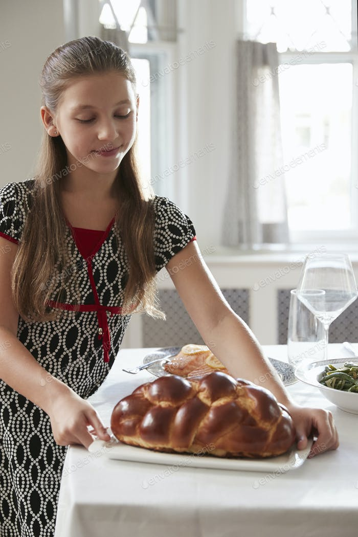 Mädchen legt Challah Brot auf Tisch für Shabbat Mahlzeit, vertikal