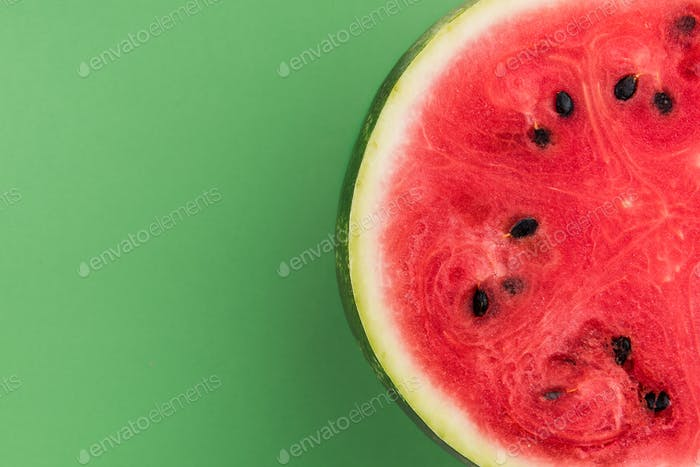 Watermelon Sliced in Half, Top View on Green Pastel Background