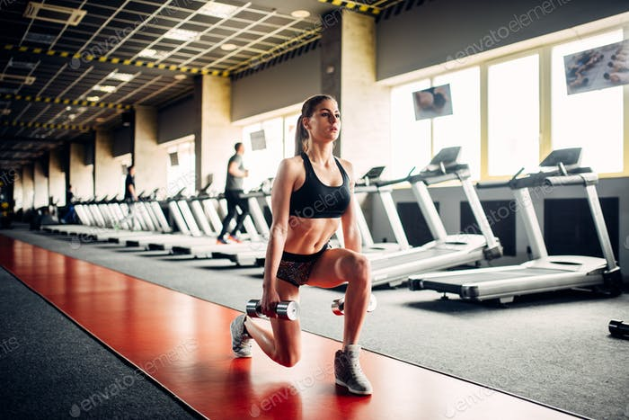 Slim woman doing exercise with dumbbells