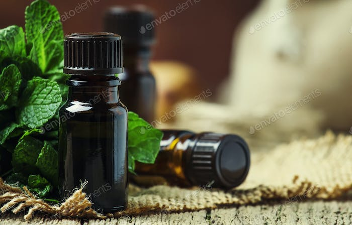 Essential oil of peppermint in a small brown bottle with fresh green mint
