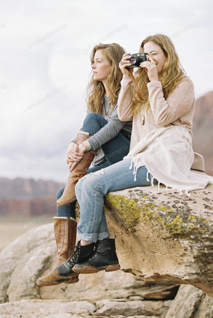 Two women sitting side by side on a rock taking a picture.