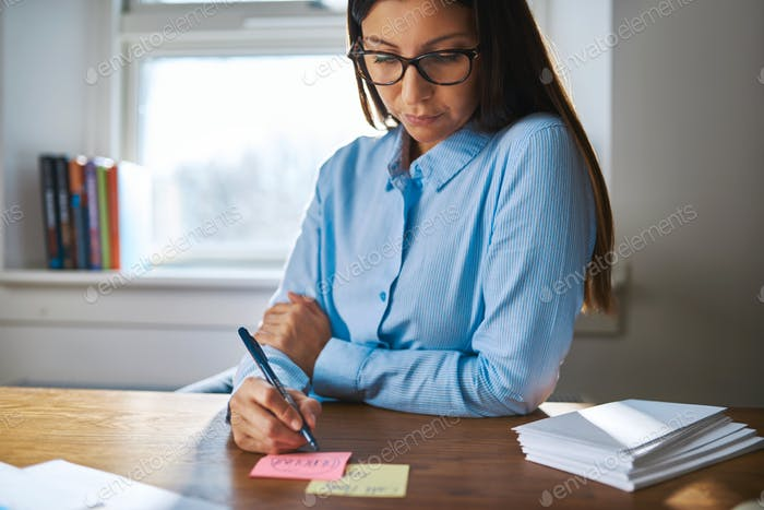 Young woman making notes in the office