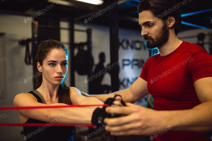 Personal trainer is motivated to show to his trainee how to get maximum from exercise