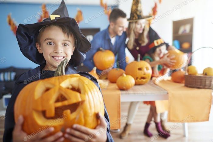 Cheerful boy and his huge pumpkin