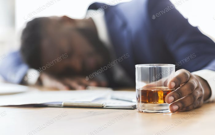 Drunk employee with glass of whiskey sleeping at working place