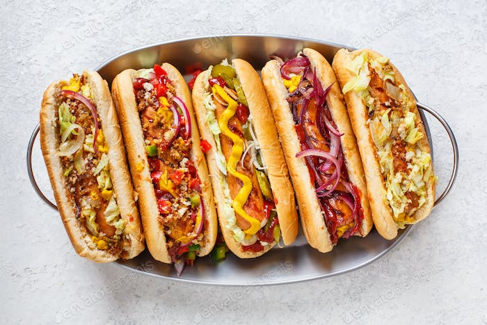 Hot dogs fully loaded with assorted toppings on a tray.