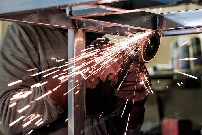 Mann in Schutzhandschuhe Schneiden Metall mit Winkelschleifer machen Funken