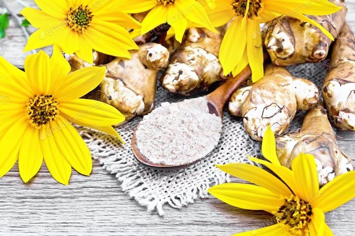 Flour of Jerusalem artichoke in spoon on old board