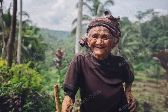 Happy senior woman with a cane in village