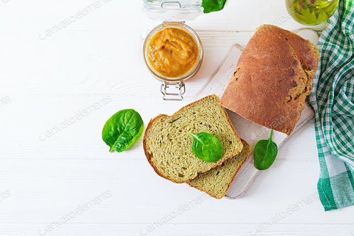 Freshly baked  spinach bread on a white wooden table. Rustic style. Bakery food.Top view