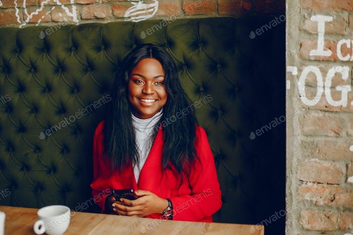 bastante negro chica en un café