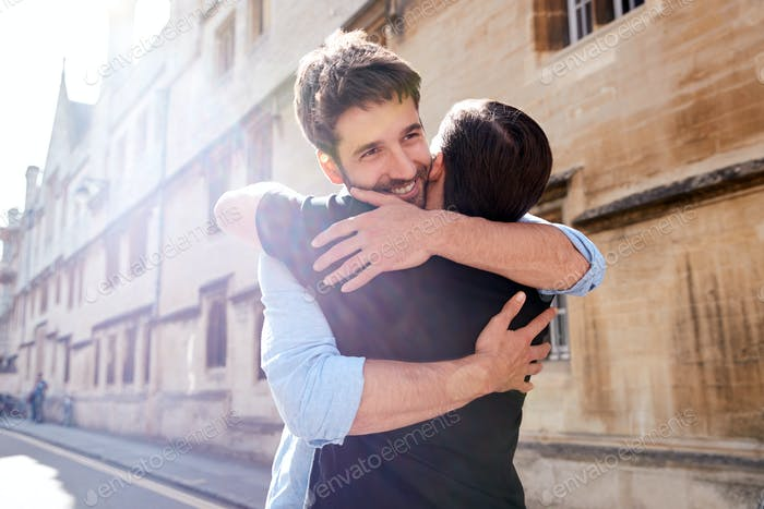 Loving Male Gay Couple Hugging Outside In City Street