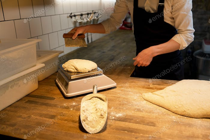 baker weighing bread dough on scale at bakery