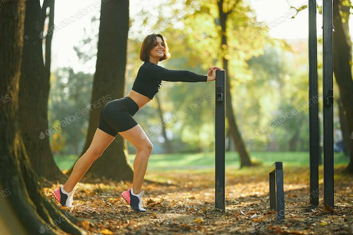 Woman in activewear posing on camera at outdoor sport ground