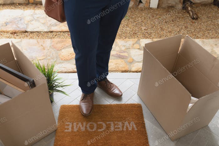 Low section of man with cardboard boxes standing on welcome mat in front of door at home