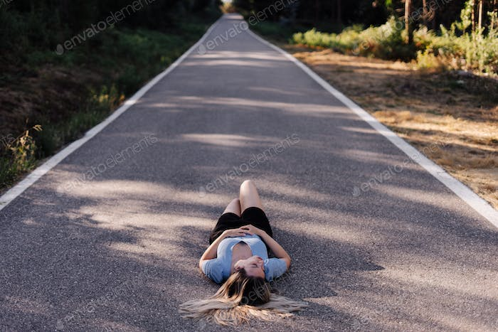 Young woman laying on a countryside road