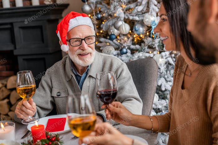 Happy senior man enjoying christmas dinner together at home with his family