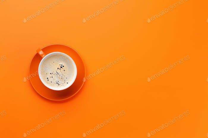 Orange coffee cup over orange background
