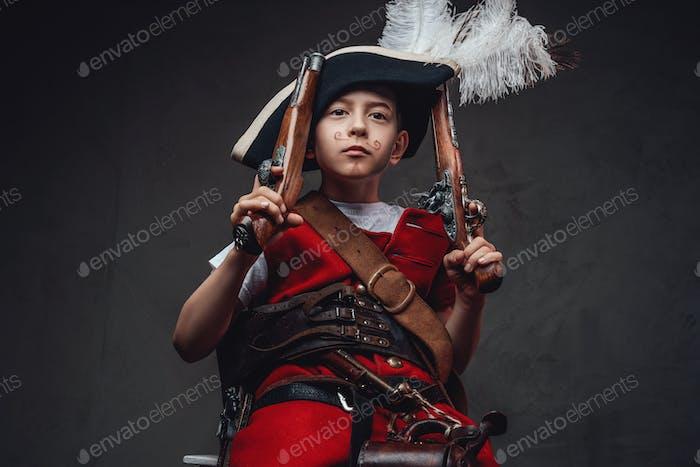 Lustiges Kind mit bemaltem Schnurrbart und Pistolen