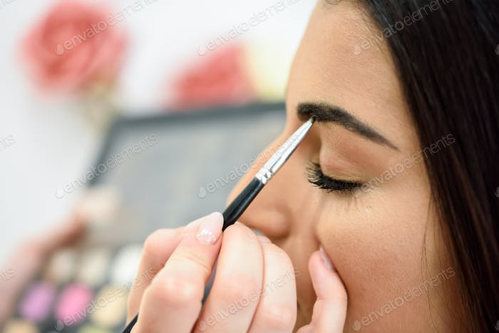Makeup artist putting make-up on an woman's eyebrows