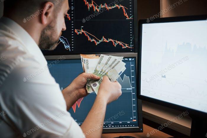 Hombre barbudo en camisa blanca tiene dinero ganado en la oficina con múltiples pantallas de ordenador