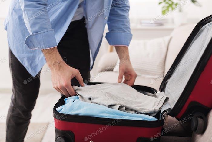 Reisekonzept. Mann packt Kleidung in Koffer