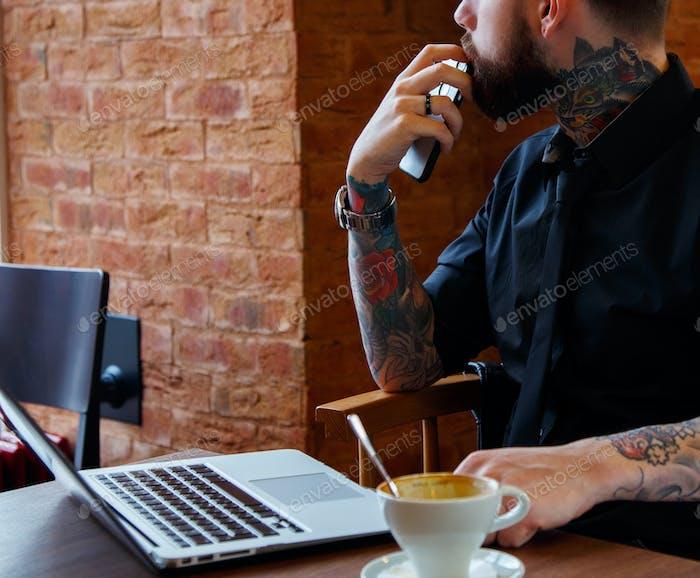 Tattoe man with beard and laptop.
