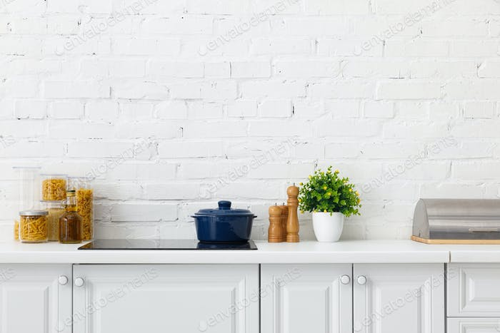 interior de la cocina blanca moderna con olla en placa de inducción eléctrica cerca de plantas y recipientes de alimentos