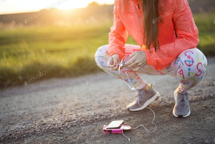 Low section of woman crouching on dirt road, holding headphones