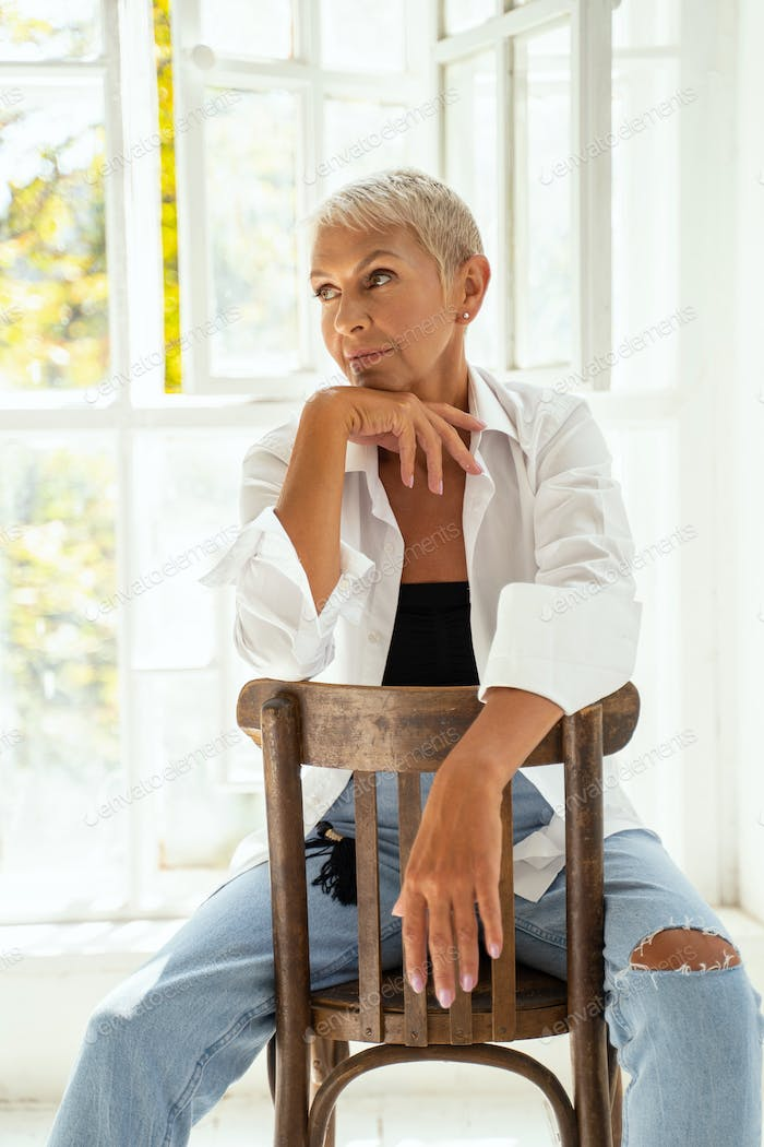 Thoughtful senior female person shooting in studio