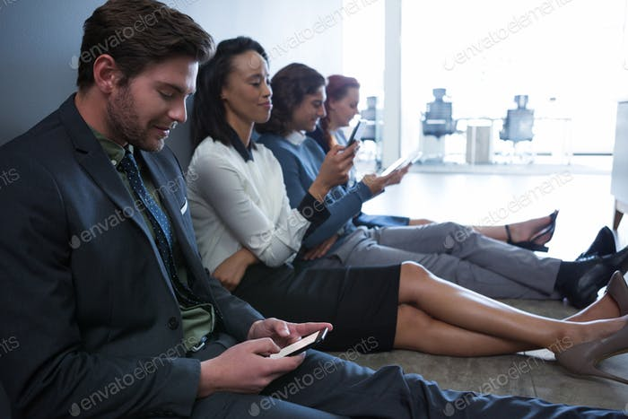 Team of business people using mobile phone