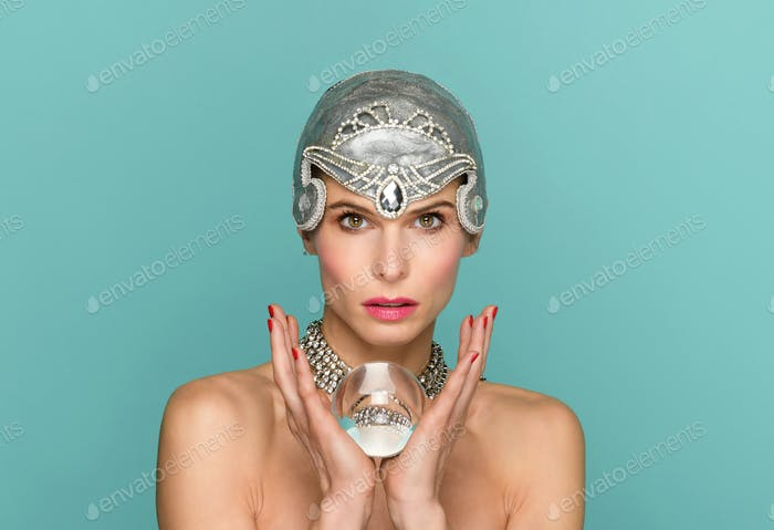 Chic woman in tiara holding a glass ball
