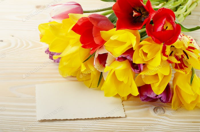 Colorful tulips and blank greeting card on natural wooden backgr