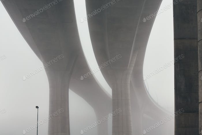 Pillars of the highway bridge in fog