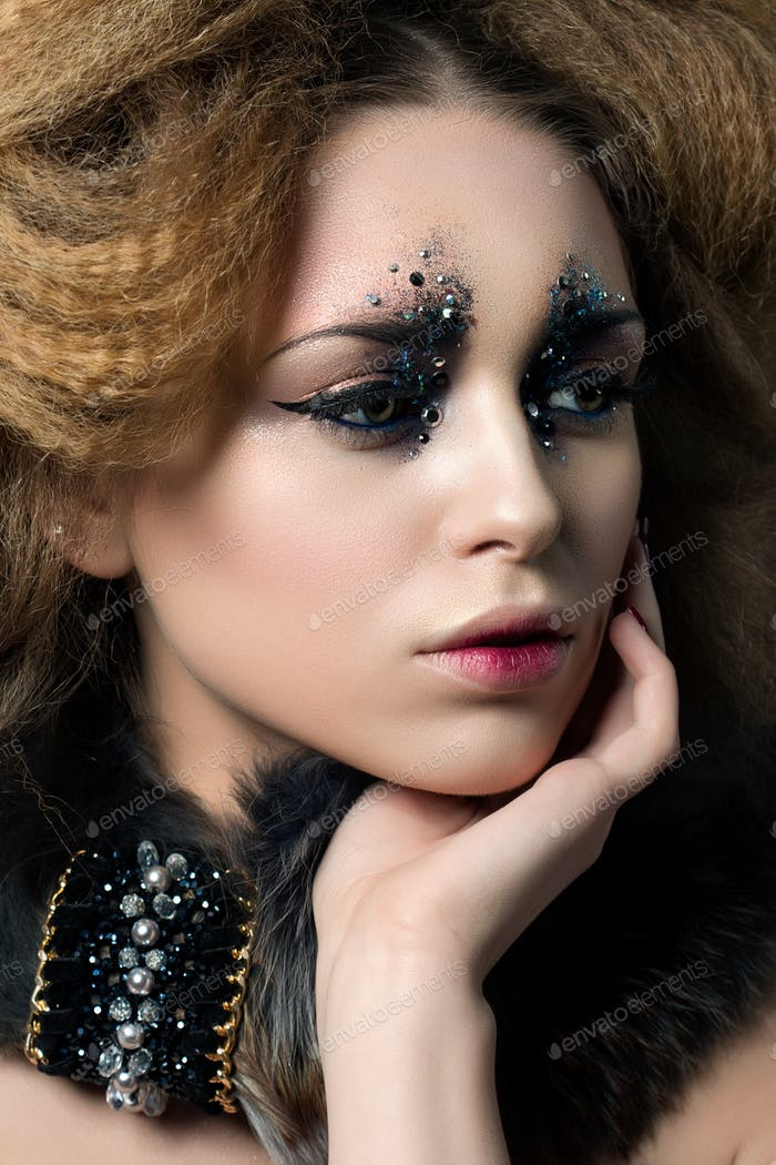 Beauty portrait of young woman with fashion makeup with rhinesto