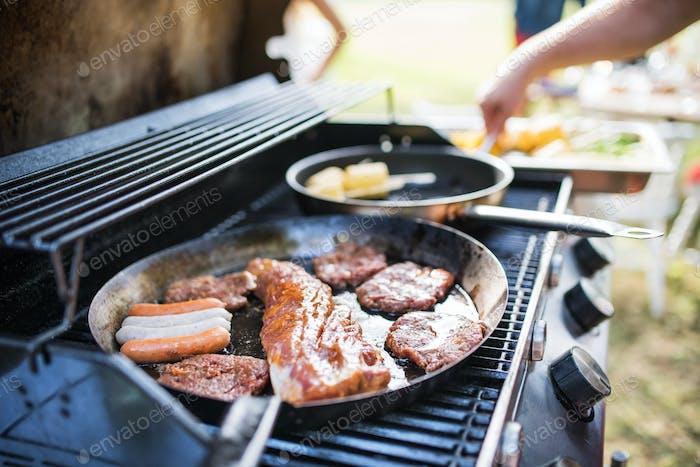 Fleisch und Wurst auf dem Grill. Gartenparty draußen im Garten.