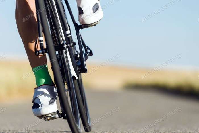 Close-up of the foot of a young man cycling.