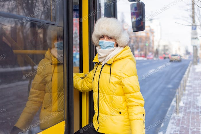 Young smiling woman walks into the bus on a winter day